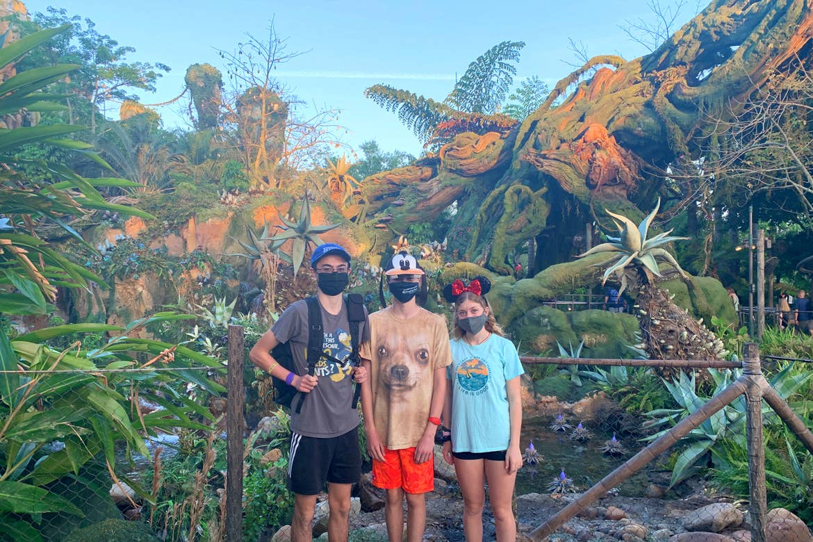 Two young men (left) and a young woman (right) wear Disney hats and safety masks near various greenery in PANDORA - World of Avatar in Disney's Animal Kingdom at Walt Disney World Resort.