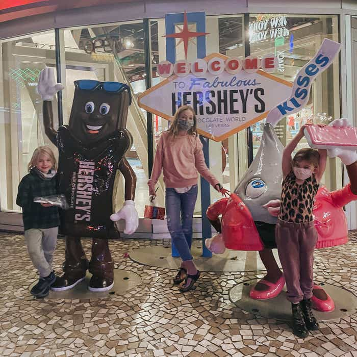 The Haby kids pose with character statues near a Las Vegas marquee replica that reads, 'Welcome to Fabulous Hershey's Chocolate World.'