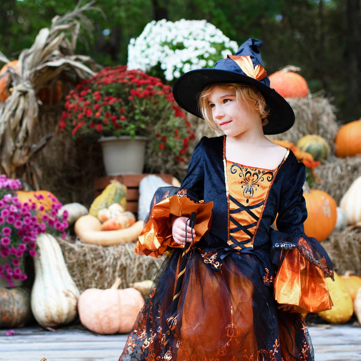 A young girl wears a witch costume near bales of hay.