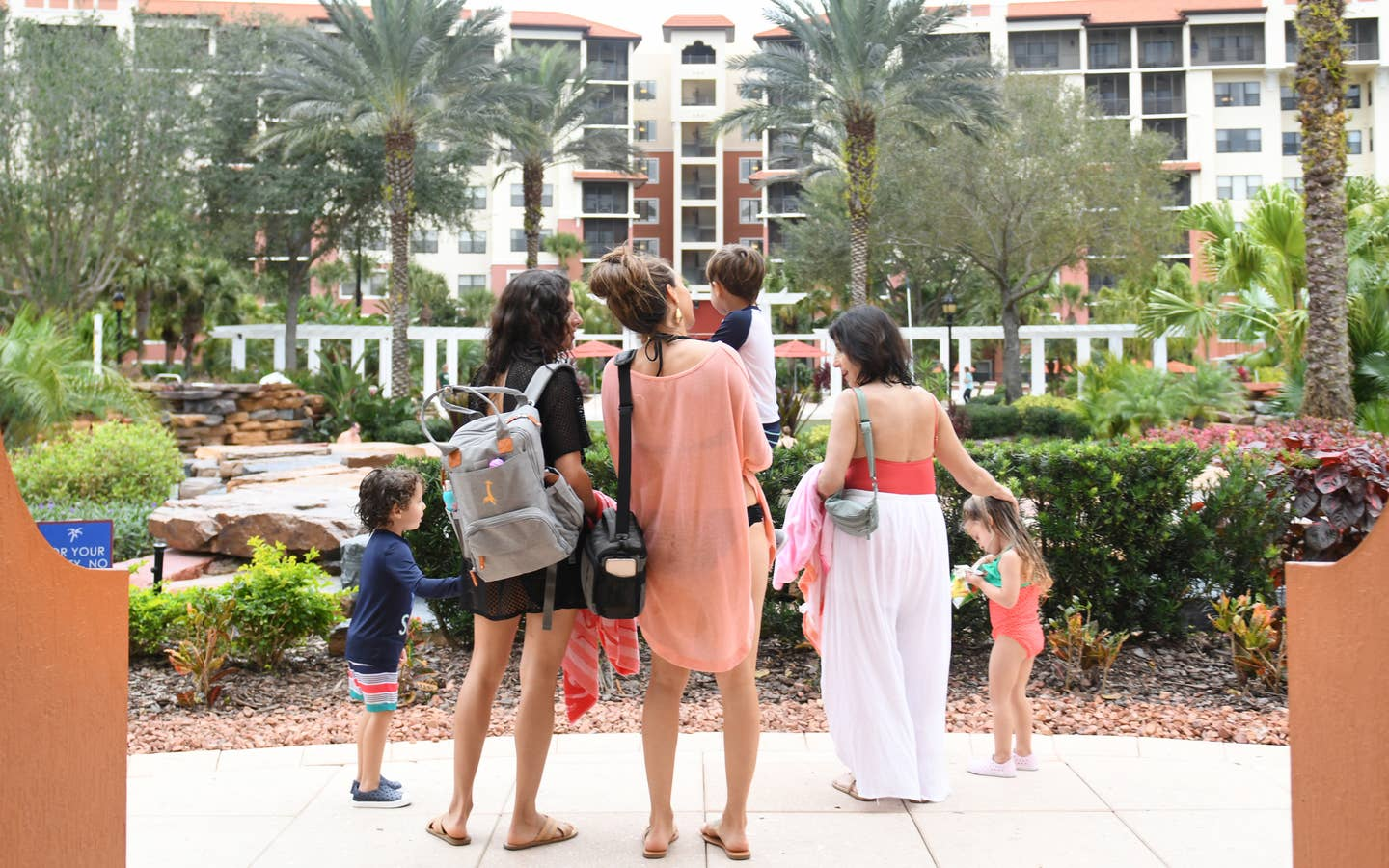 Family standing outside of a large resort building with large palm trees and tropical plants