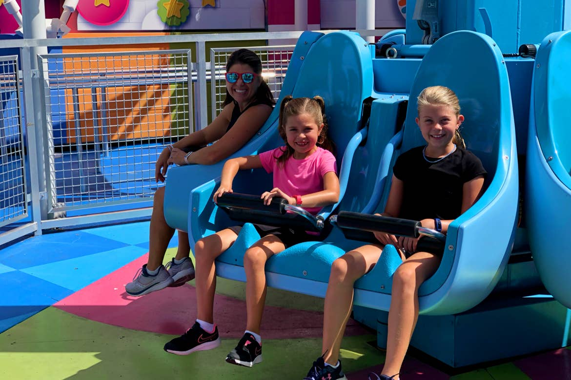 A woman (left) and two girls (right) are seated on a vertical ride vehicle.