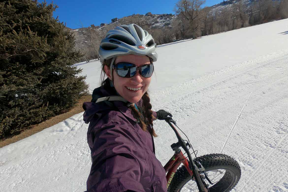 Featured Contributor, Jessica Averett, wears a winter jacket, sunglasses, and white bike helmet while riding a Fat Tire bike in the snow in front of the mountains.