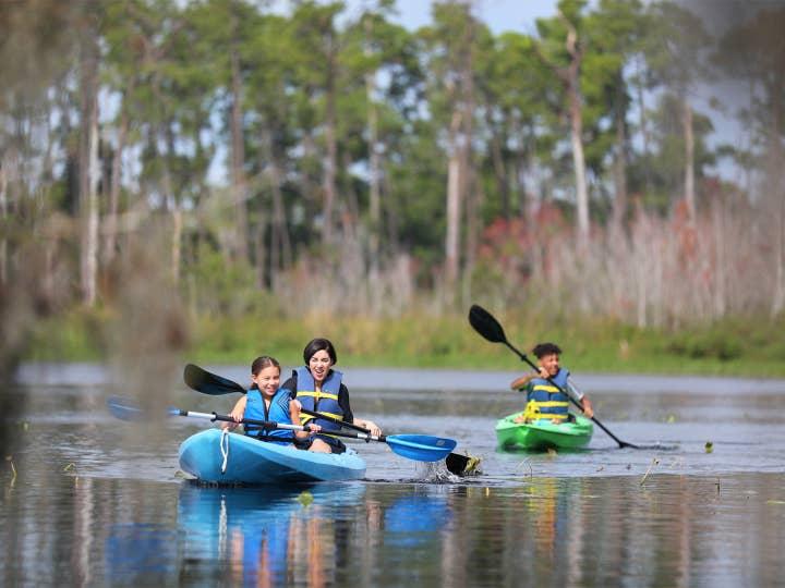 Kids kayaking in lake with watersport rentals at Orange Lake Resort near Orlando, Florida.