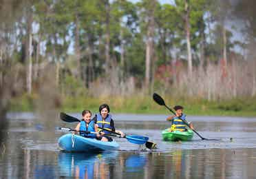 Kids kayaking in lake with watersport rentals at Orange Lake Resort near Orlando, Florida.