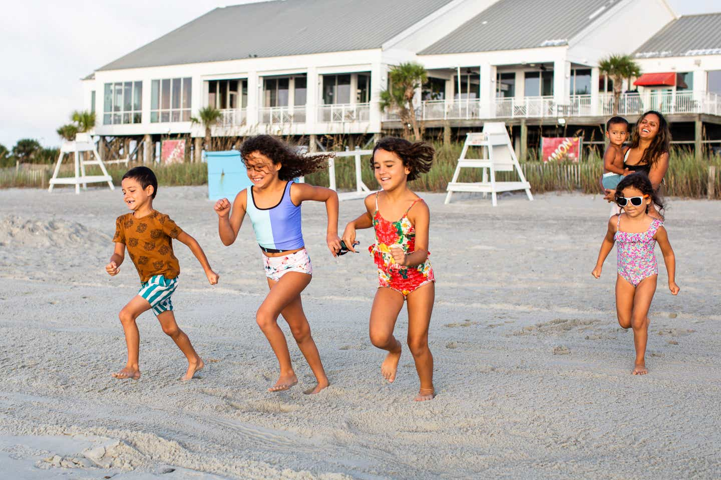 Brenda and her family run from their resort to the beach in swimwear.