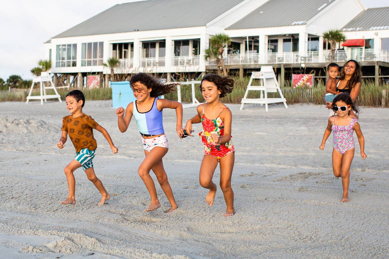 Brenda and her family run from their resort to the beach in swimwear.