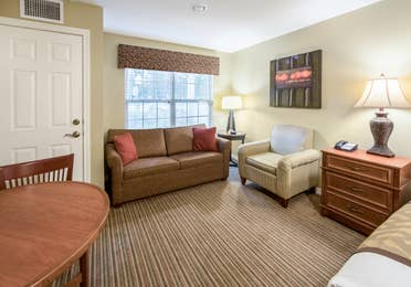 Living area with chair and accent chair in a studio room at Piney Shores Resort in Conroe, Texas