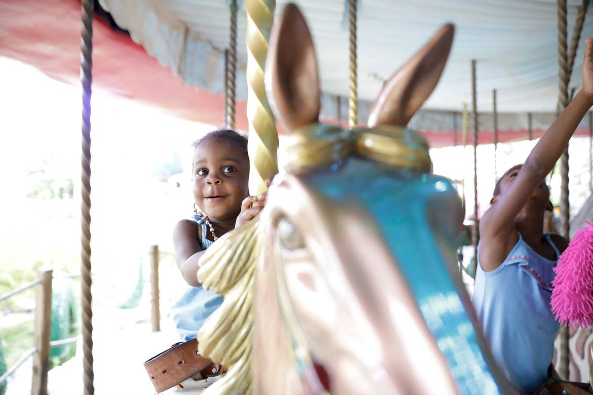 A Give Kids the World Villager rides a carousel in the Town Square (Photo take prior to COVID-19.)