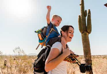 Young child on woman's shoulders in McDowell Sonoran Preserve near Scottsdale Resort.
