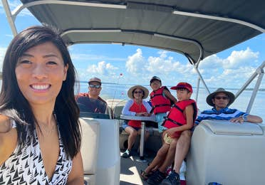 An Asian woman wearing a white swimsuit on a boat with her multigenerational family on a lake.