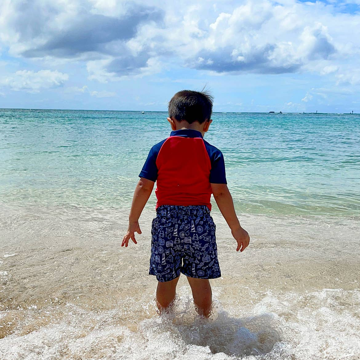 Featured Contributor, Danny Pitaluga's son, Joey, stands in the sand on the beach in swimwear as waves roll in.