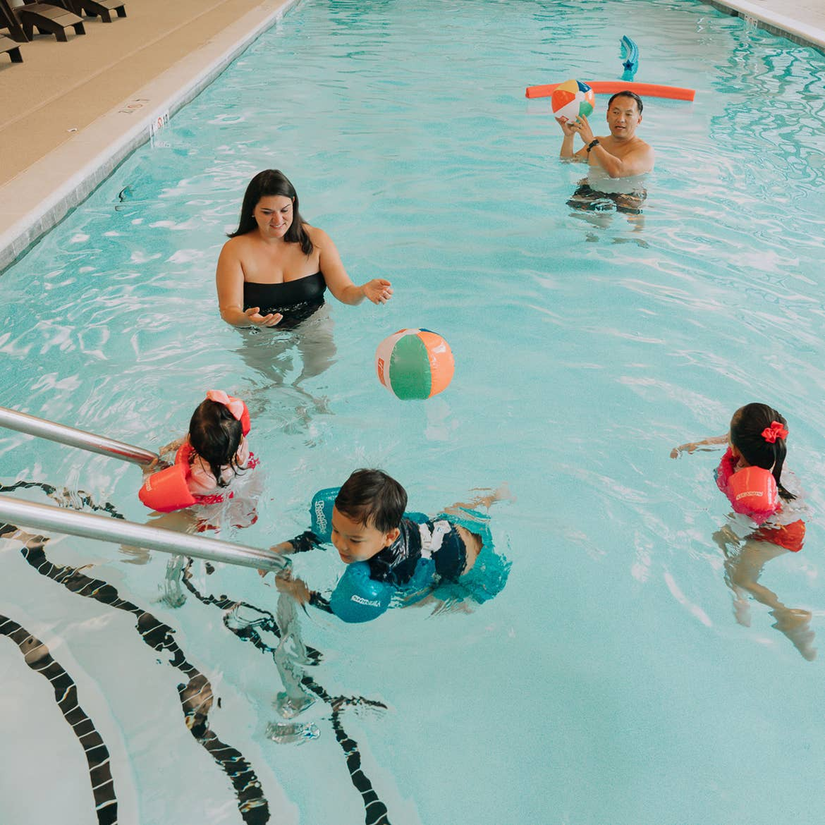 Featured Contributor, Angelica Kajiwara (left), and her family swim in a pool wearing swimming floaties at our Williamsburg resort in Williamsburg, Virginia.