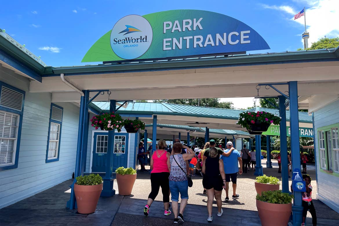 Several guests walk under the entrance queue of SeaWorld Orlando with signage that reads 'Park Entrance' with green and blue hues.
