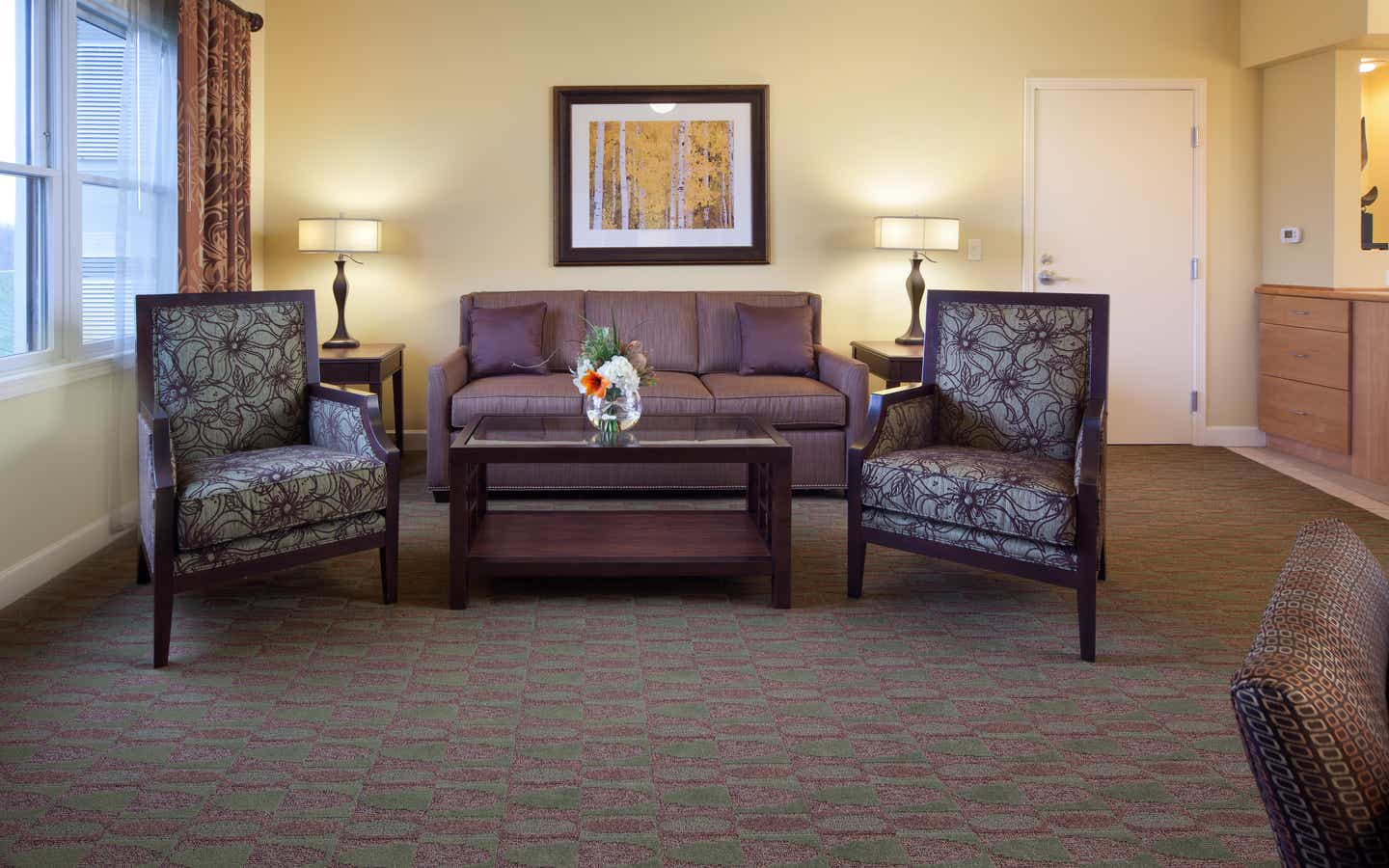 Living room with couch and two accent chairs in a one-bedroom villa at Lake Geneva Resort