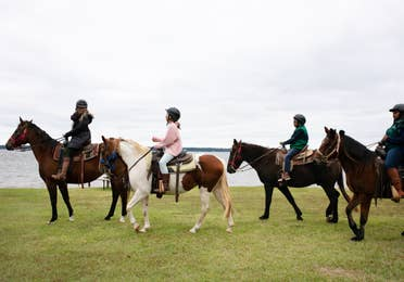 Four people horseback riding near a body of water