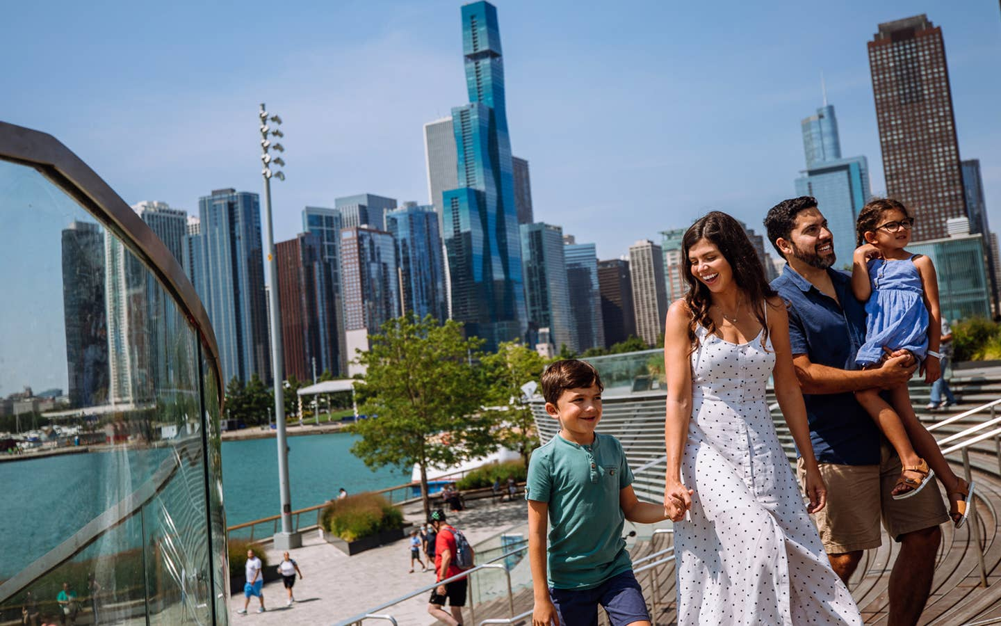 A woman, a man, a young boy and girl walk near the Chicago Skyline.