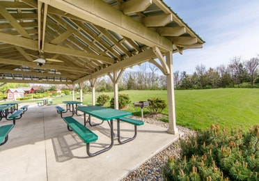 Outdoor picnic area with covered shelter and green picnic tables at Fox River Resort in Sheridan, Illinois