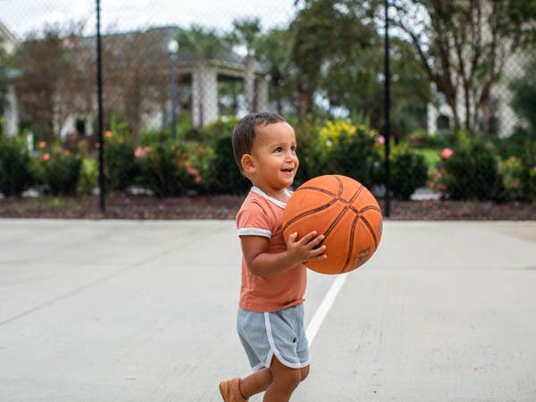 Young child holding basketball on basketball court at South Beach Resort in Myrtle Beach, South Carolina.