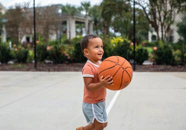 Young child holding basketball on basketball court at South Beach Resort in Myrtle Beach, South Carolina