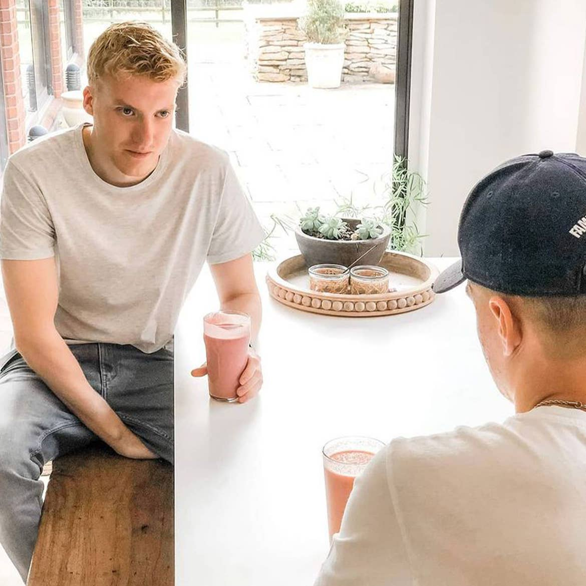 Featured Contributor, Ninka-Bernadette Mauritson's son Bertram, sits at a table holding the smoothie that started his transition into healthier alternatives.