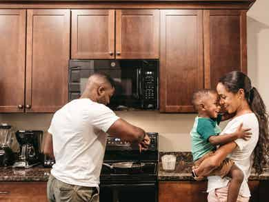 Family cooking a meal in their villa's full kitchen.