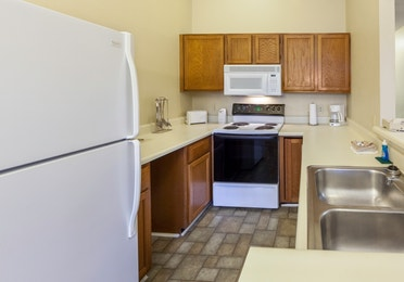 Kitchen with fridge, oven, microwave, and sink in a two-bedroom cabin at Ozark Mountain Resort in Kimberling City, Missouri