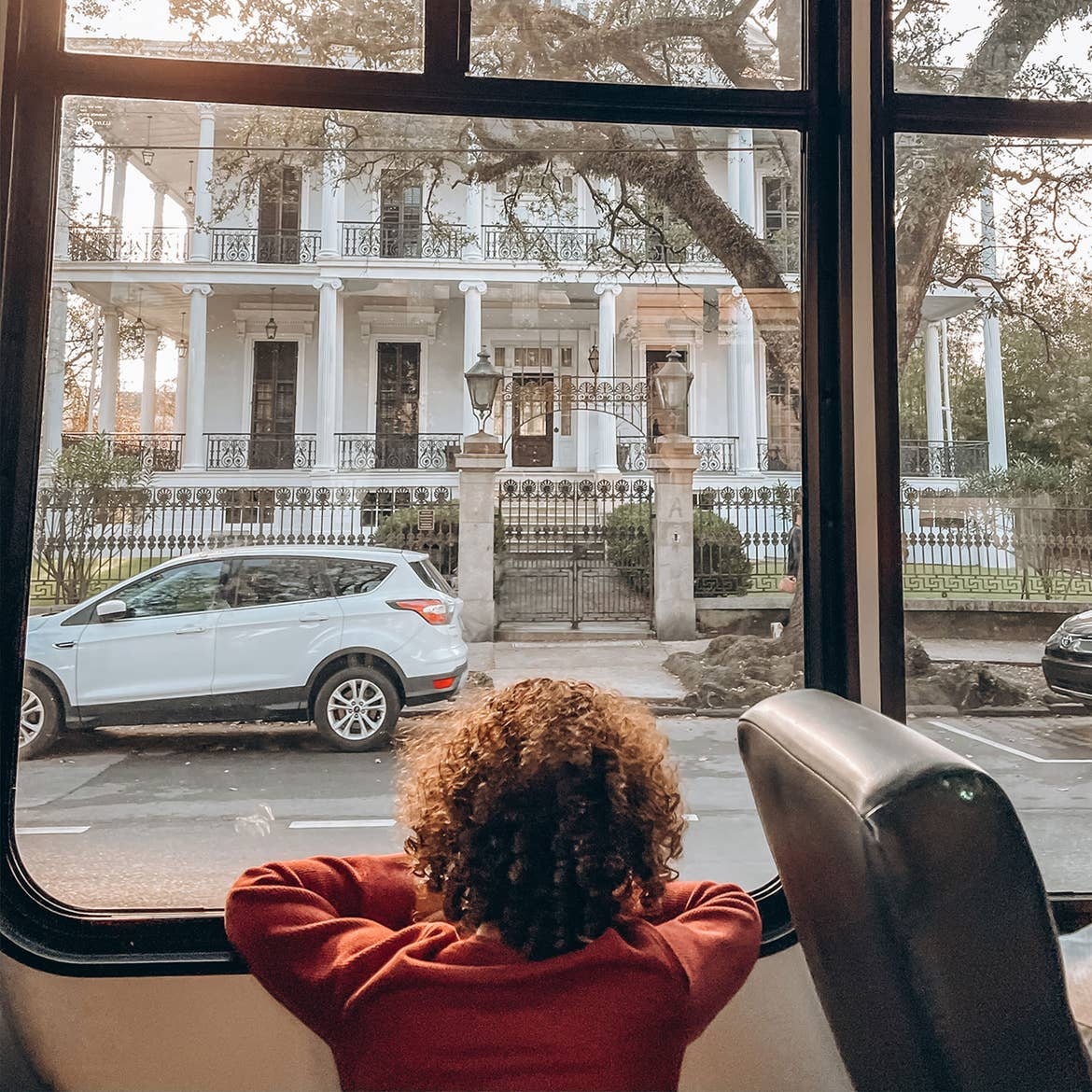 Featured Contributor, Sally Butan of @butanclan's son, Alex, looks out a bus window at the exterior of a white house in the Garden District of New Orleans, Louisiana.
