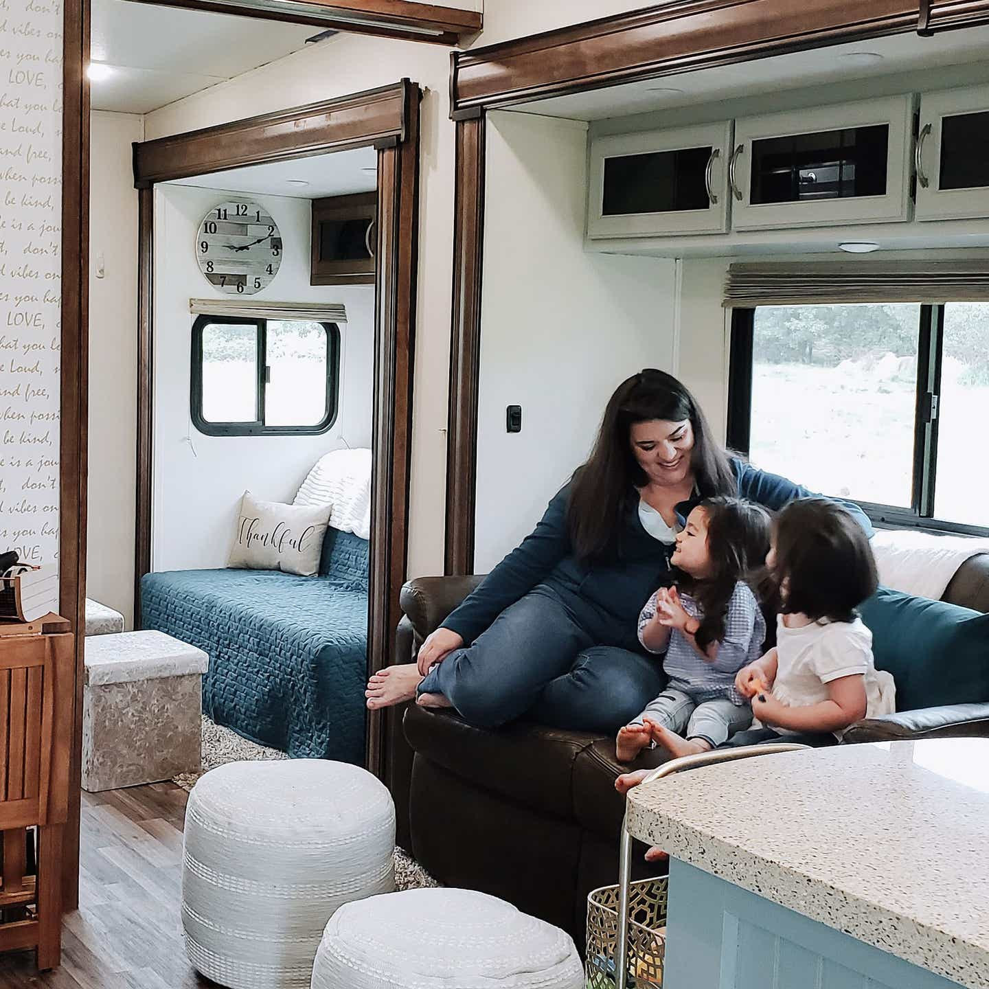 Angelica (left) sits with her two daughters in their RV.