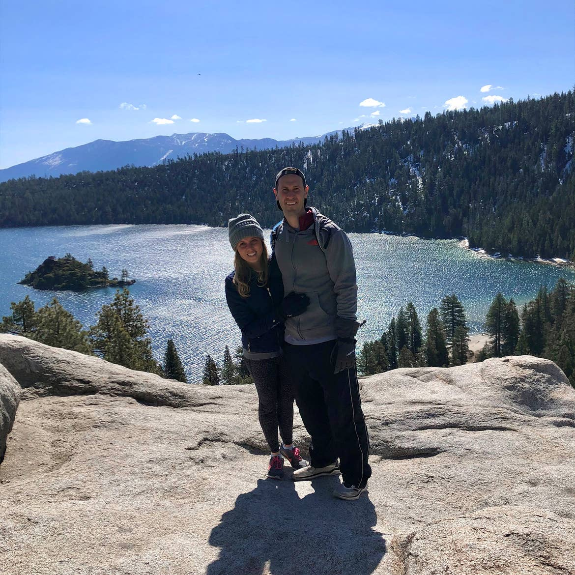 A woman (left) wears a grey beanie and black leather jacket and gloves while hugging a man (right) wearing a grey sip-up hoodie and green beanie in front of a mountain range at Lake Tahoe, Nevada.