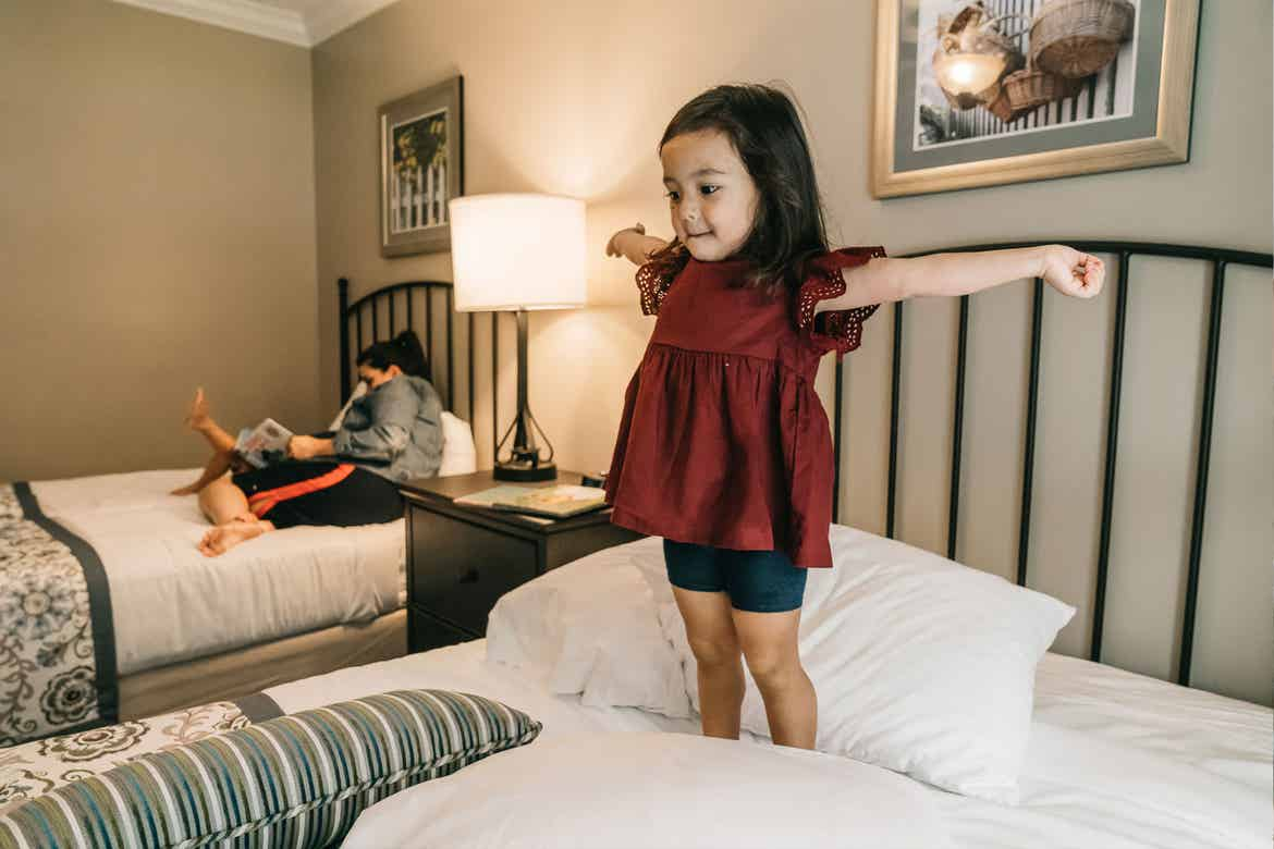 Featured Contributor, Angelica Kajiwara's daughter wears a burgundy blouse while standing and stretching on the bed in the villa of our Williamsburg resort in Williamsburg, Virginia.