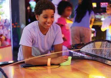 A young boy leaning on an air hockey table in an arcade