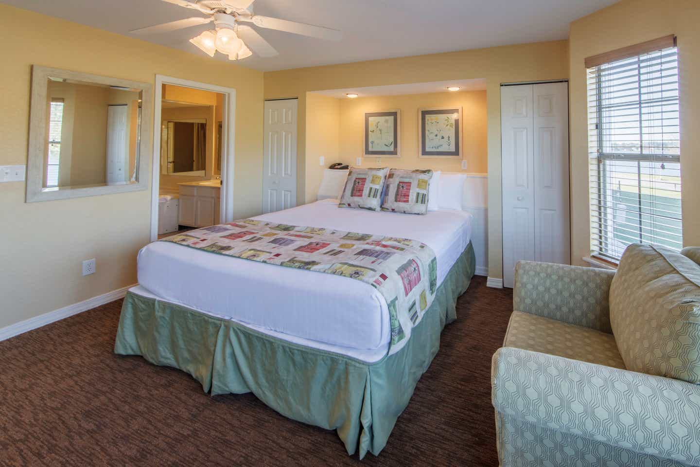Master bedroom with king bed and seating area in a presidential two bedroom villa at Piney Shores Resort in Conroe, Texas