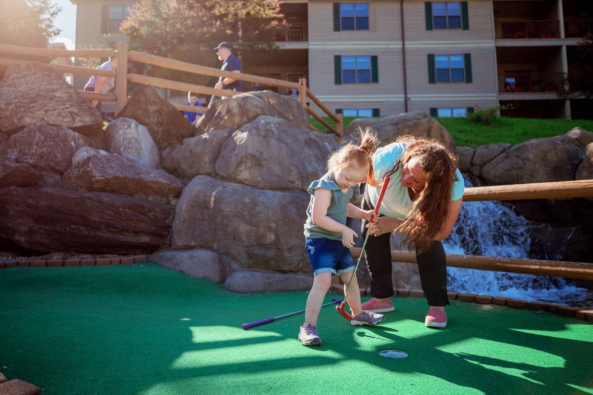 A young girl (left) and woman (right) play on a mini golf course.