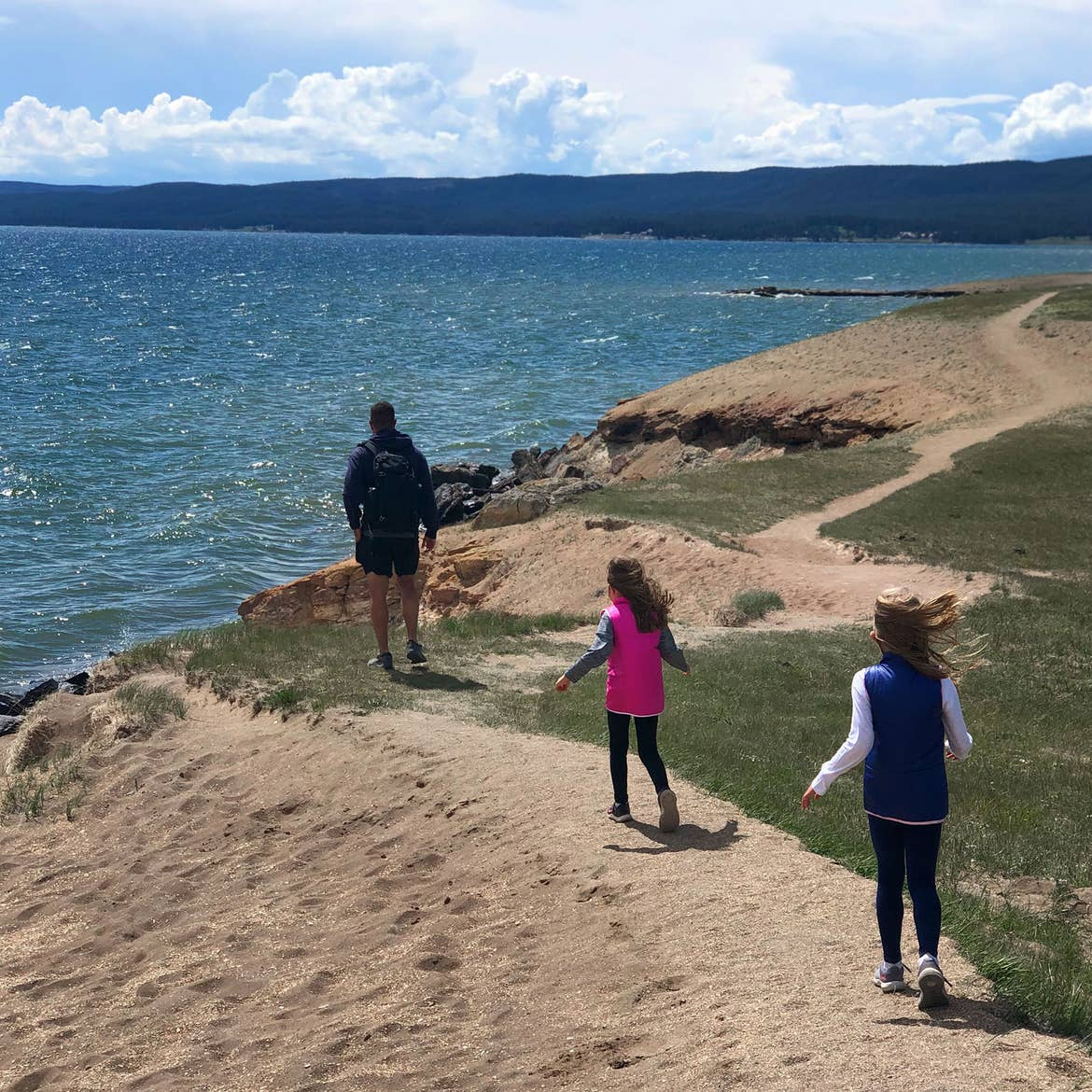 Author, Chris Johnstons' husband, Josh (far-left), walks towards the lake at Yellowstone National Park with their daughters, Kyndall (front-right), and Kyler (middle.