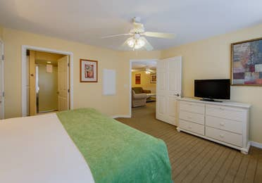 Bedroom with a flat screen TV, attached bathroom, and ceiling fan in a one-bedroom Presidential villa at Hill Country Resort in Canyon Lake, Texas