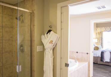 Bathroom with walk-in shower, soaking tub, and complimentary robe in a four bedroom Signature villa in River Island at Orange Lake Resort near Orlando, Florida