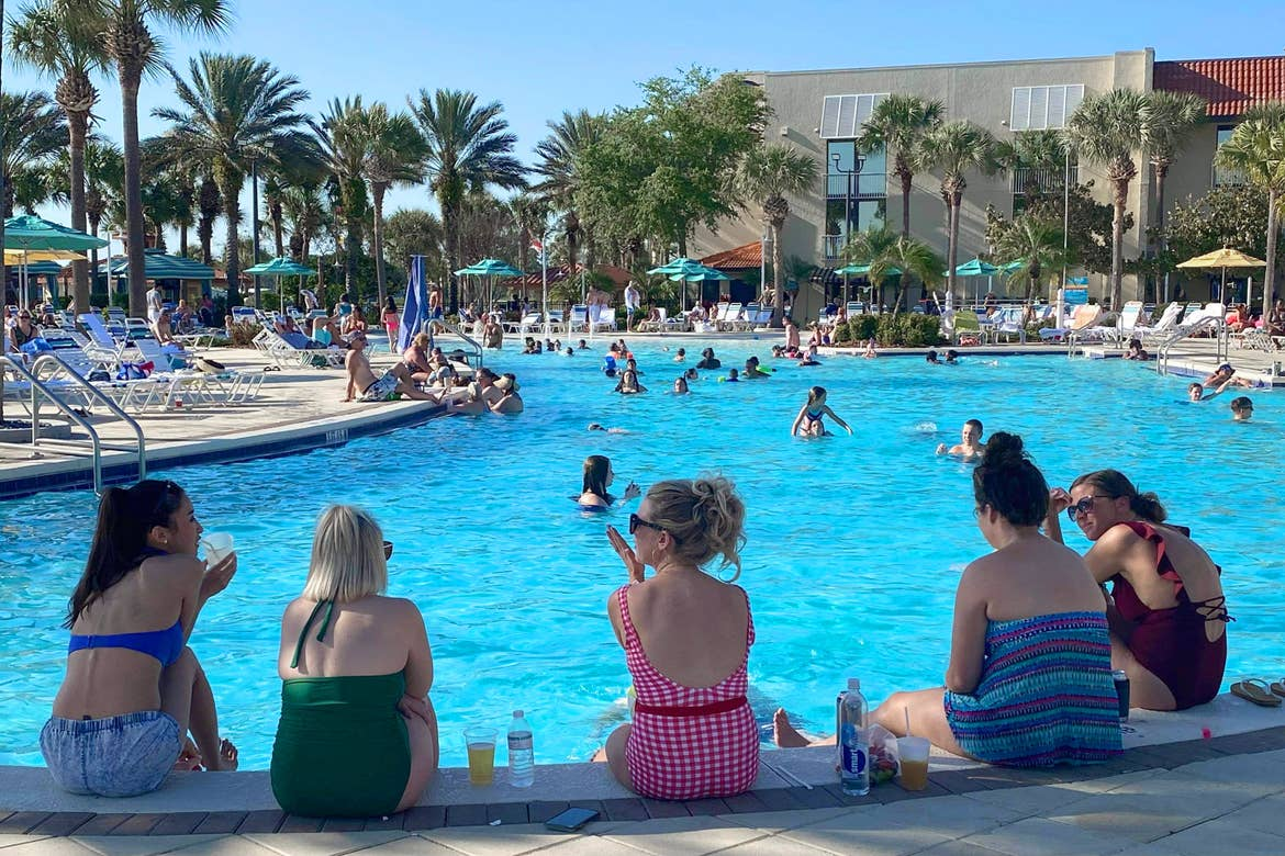 A group of caucasian women in various colored swimsuits sit at the edge of a pool surrounded by a resort facade and palm trees under a blue sky.
