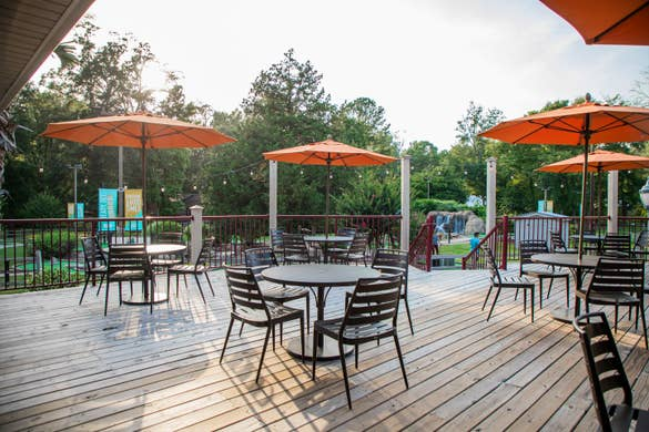 The patio of our Activities Outpost with patio tables and umbrellas at our Villages Resort located in Flint, Texas.