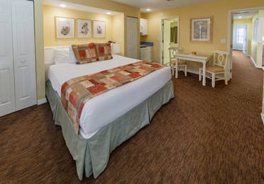 Bedroom with king bed and sitting area in a presidential two bedroom villa at Piney Shores Resort in Conroe, Texas