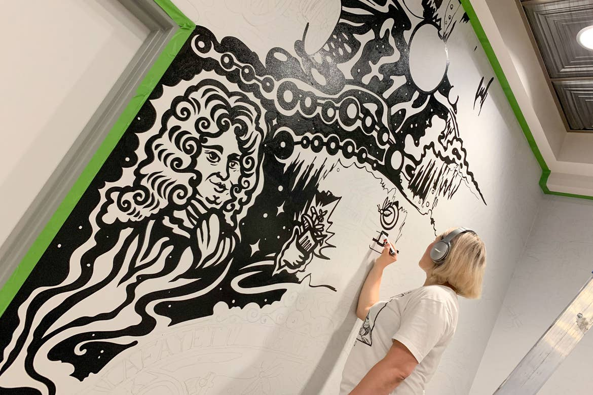 Muralist, Mila Sketch, wears headphones as she paints over her outlined mural art featured in the lobby of our resort in New Orleans, Louisiana.