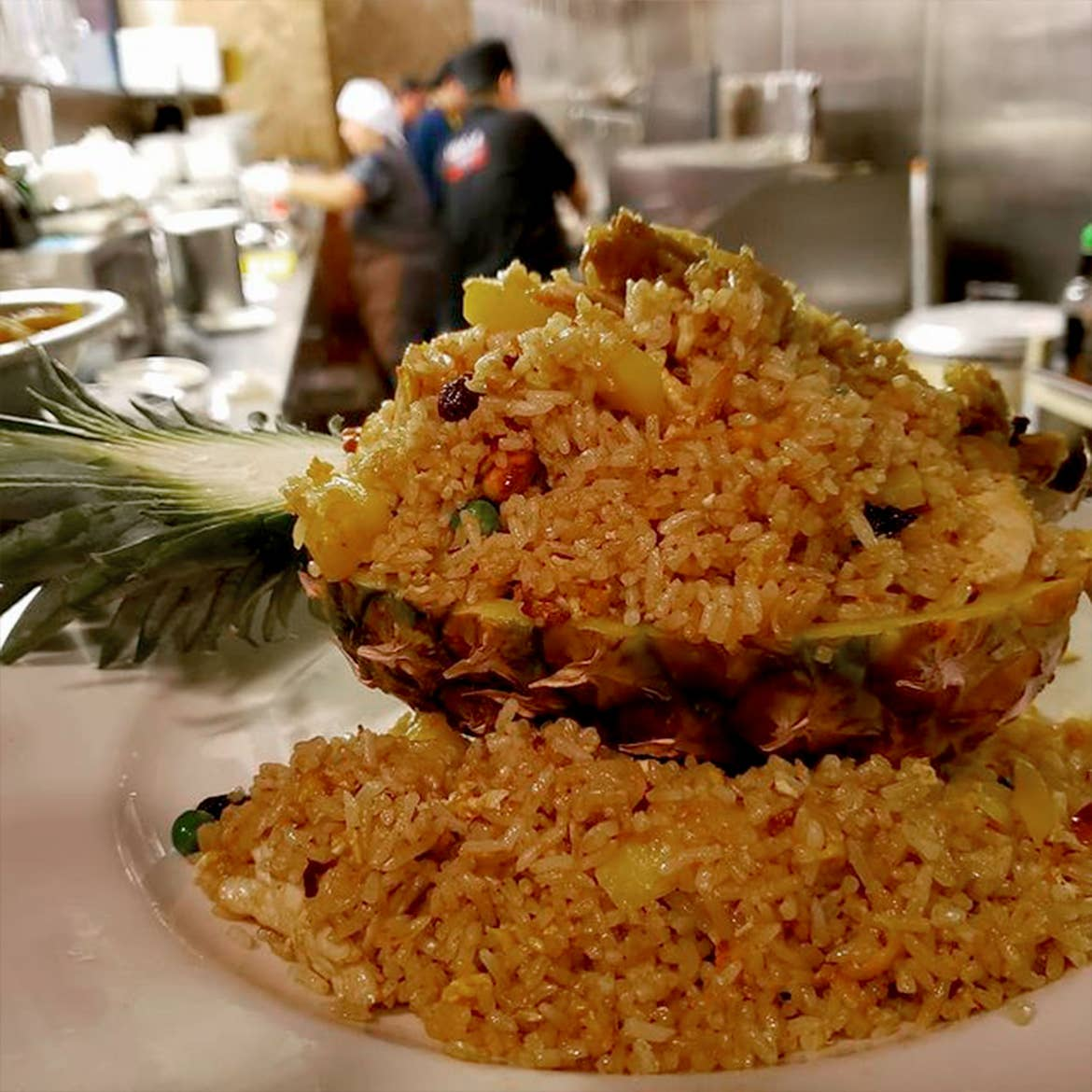 Pineapple fried rice on a plate sitting in the expo window of the kitchen ready to be served.