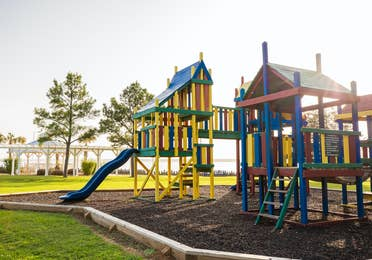 Outdoor playground painted in yellow, green, red and blue at Villages Resort in Flint, Texas.