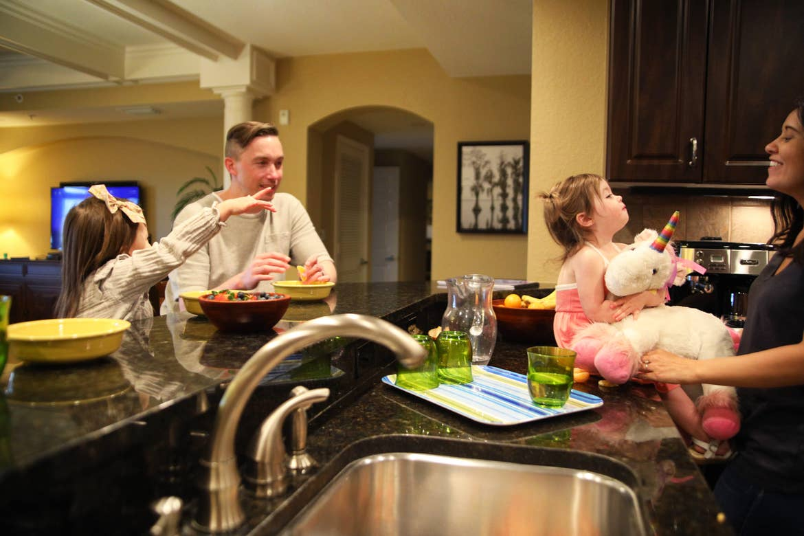 Mia of and her family sitting around the kitchen in their villa at Orange Lake Resort