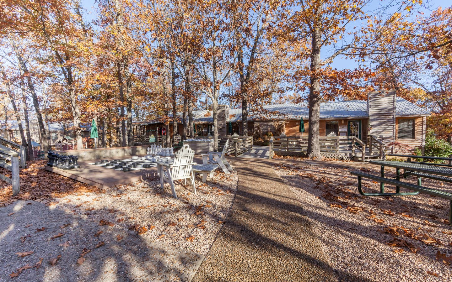 Outdoor picnic tables surrounded by trees at Ozark Mountain Resort in Kimberling City, MO.