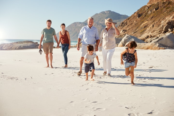 Family walking in the sand at a beach surrounded by large rocking hills