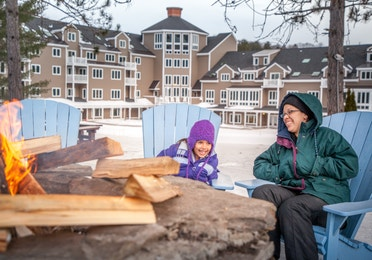 A woman and a young girl sitting by the fire pit in the winter in front of Mount Ascutney Resort