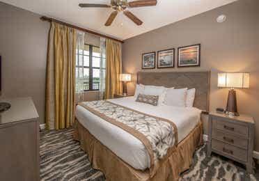 Bedroom with king bed, large window, and ceiling fan in a three-bedroom villa at Sunset Cove Resort in Marco Island, Florida