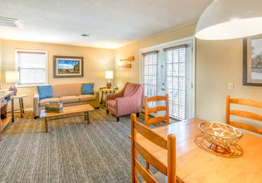 Living room and dining area in a one bedroom villa at Oak n' Spruce Resort in South Lee, Massachusetts