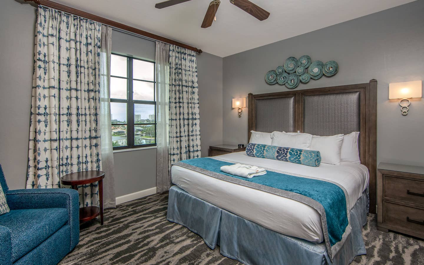 Bedroom with king bed, large window, seating area, and ceiling fan in a three-bedroom villa at Sunset Cove Resort in Marco Island, Florida