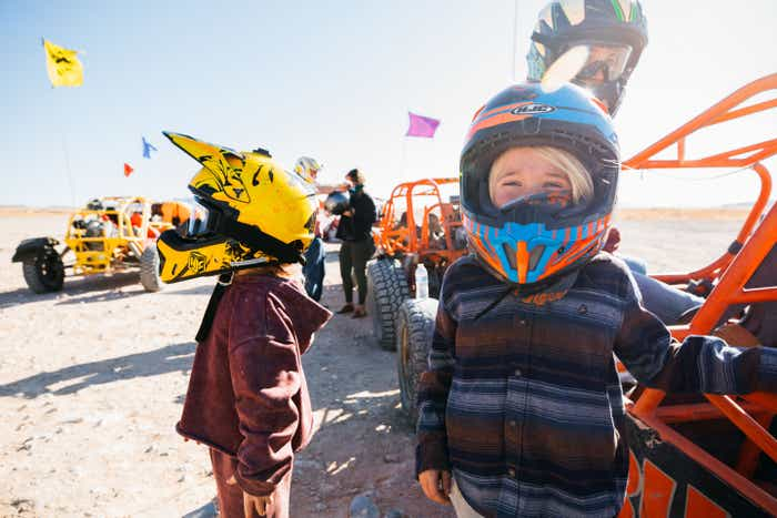 The Haby kids wear safety helmets next to their Sunbuggy in the sandy dunes near our Desert Club Resort located in Las Vegas, Nevada.